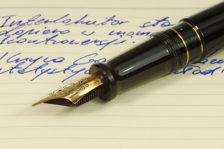 Fountain pen with gold, ornate nib on a notebook. Stockfoto