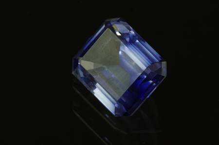 synthetic: Sapphire %u2013 grinded synthetic corundum on black background. Emerald cut. Stock Photo