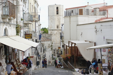 foggia: Monte Sant Angelo, Italy - September 11, 2015: center of the historic town on the Gargano Peninsula in the province of Foggia. On the historic street stalls with souvenirs. At the end of the street you can see the tower of the Shrine of Saint Michael the