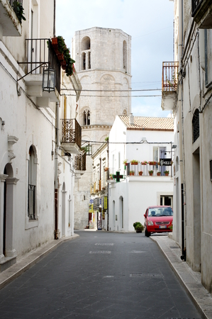 foggia: Monte Sant Angelo, Italy - September 11, 2015: center of the historic town on the Gargano Peninsula in the province of Foggia. At the end of the street you can see the tower of the Shrine of Saint Michael the Archangel.