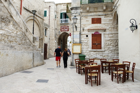foggia: Vieste, Italy - September 09, 2015: center of the historic town on the Gargano Peninsula in the province of Foggia. In the image are visible tourists, historic buildings and tavern. Editorial