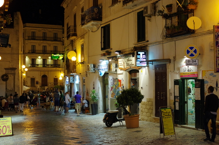 foggia: Rodi Garganico, Italy - September 12, 2015: center of the historic town on the Gargano Peninsula in the province of Foggia. Evening street life: open shops and dining, strolling locals and tourists.