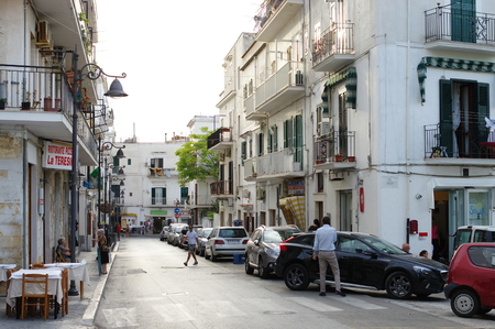 foggia: Vieste, Italy - September 16, 2015: the town on the Gargano Peninsula in the province of Foggia. In the image are visible street typical for the region, buildings and tavern. On the street there are residents of the city and tousists. Editorial