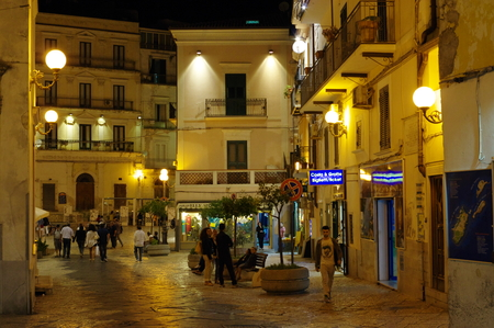 Rodi Garganico, Italy - September 12, 2015: center of the historic town on the Gargano Peninsula in the province of Foggia. Evening street life: open shops and dining, strolling locals and tourists.