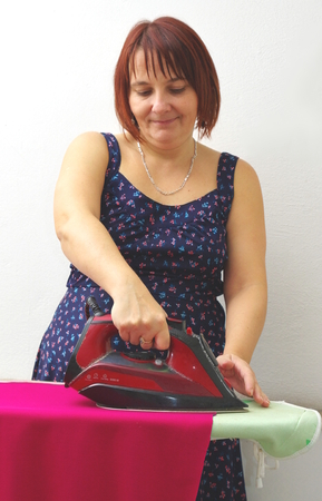 ironing board: Household chores - ironing. Woman irons red cloth on the ironing board.