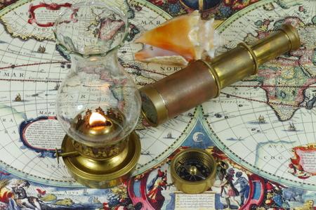 kerosene: Old telescope, compass, kerosene lamps and seashell lying on an old map of the world.