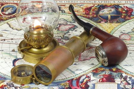 kerosene: Old spyglass, pipe, compass and kerosene lamp lying on a vintage map of the world.