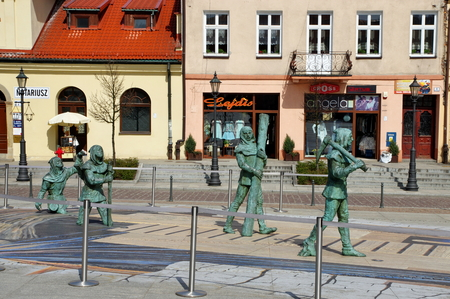 miners: Wieliczka, Poland - April 04, 2016, Upper Square. Sculptures of ancient salt miners. In the background are the town houses.