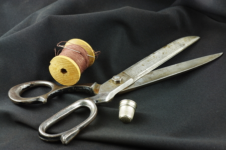 undulating: Old dressmaker shears, wooden spool of thread with a needle and a thimble. On a dark, undulating fabric. Stock Photo
