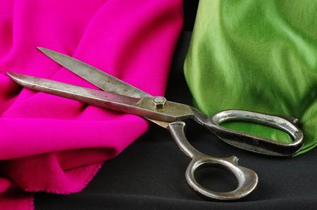 dressmaker: Old dressmaker scissors on a colored, creased fabrics. Stock Photo