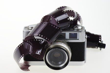 analog camera: Old rangefinder analog camera system 135 and the photographic film on the white background.