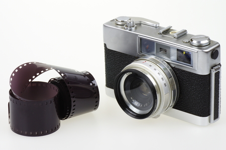 rangefinder: Old rangefinder analog camera system 135 and the photographic film on the white background.
