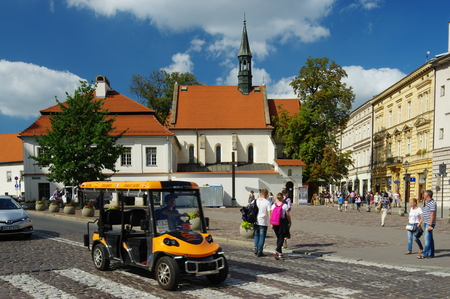 giles: Krakow, Poland - August 25, 2016: St. Giles street. On the left there is the Church of St. Giles, on the right historic townhouses standing along the street. On the street is electric vehicle to carry tourists. Editorial