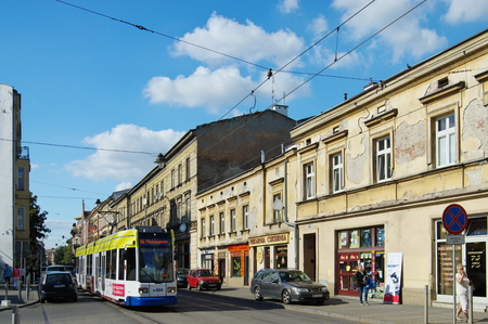building monumental: Krakow, Poland - August 25, 2016: Karmelicka street. Tram and monumental townhouses standing along the street.