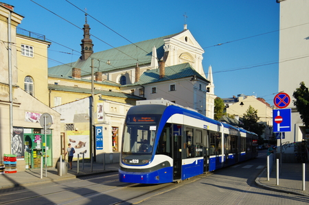 building monumental: Krakow, Poland - August 25, 2016, Karmelicka street. Tram on the street, behind him Carmelite Church.