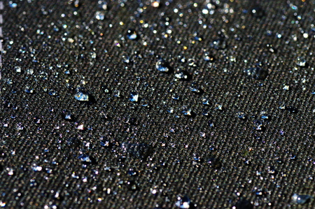 water repellent: Drops of water on a black impregnated material in the light of the sun.