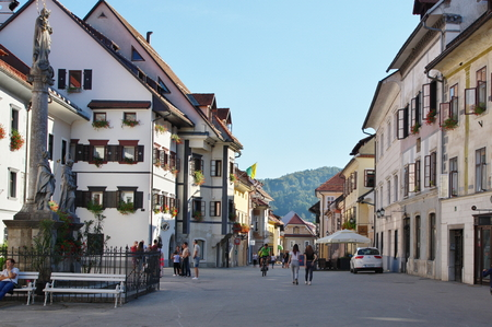 commune: Commune Skofja Loka, Skofja Loka, Slovenia - September 25, 2016, the old town, Mestni trg (City Square). Typical buildings, windows decorated with flowers. Some people are on the street. On the left there is statue of Saint Mary. Editorial