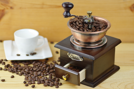 Old-style manual coffee grinder on a rustic table with wooden planks. Around the mill are scattered coffee beans. Near the mill stands empty white cup.
