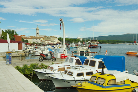 Krk, Croatia - September 19, 2016, a town in the south of the island of Krk. It is a tourist resort, preserved fragments of buildings from Roman times. Harbor. On the waterfront moored many boats and yachts. Editorial
