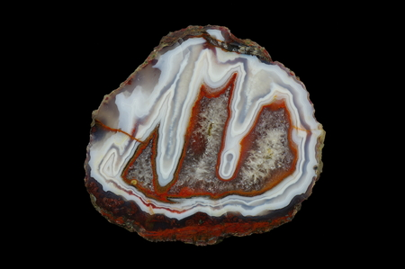 A cross section of the stalactite agate stone with quartz geode. Multicolored silica rings with colored metal oxides are visible. Origin: Asni, Atlas Mountains, Morocco. Stock Photo