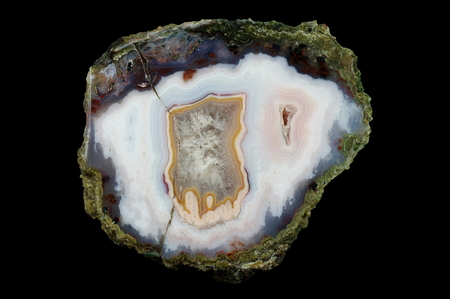 A cross section of the agate stone. At the top are chalcedony stalactites, the rest is filled with quartz. Multicolored silica bands colored with metal oxides are visible. Origin: Asni, Atlas Mountains, Morocco. Stock Photo