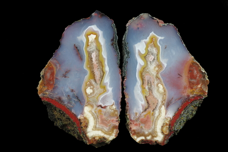 A cross section of the agate stone. A colorful center is in the blue chalice and pseudomorphs are on the shores. Multicolored silica bands colored with metal oxides are visible. Origin: Asni, Atlas Mountains, Morocco. Stock Photo