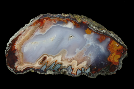 reverse: A cross section of the agate stone. At the bottom are the chalcedony stalactites (in reverse position). Multicolored silica rings colored with metal oxides are visible. Origin: Asni, Atlas Mountains, Morocco. Stock Photo