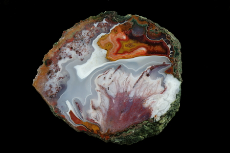 A cross section of the agate stone. At the top is concentic agate, at the bottom is a colored pseudomorphosis after dissolved minerals. Multicolored silica rings colored with metal oxides are visible. Origin: Asni, Atlas Mountains, Morocco.