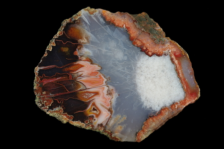A cross section of the agate stone. Built with many pseudomorphs - on the right after the concentrate of very fine crystals, in the center of the needle-shaped crystals, the left after large crystals of calcite. Multicolored silica bands colored with meta