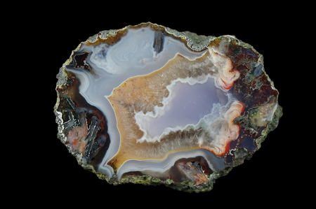 A cross section of the agate stone. Blue-green chalcedony and quartz, on the left is a pseudomorph. Multicolored silica bands colored with metal oxides are visible. Origin: Asni, Atlas Mountains, Morocco.
