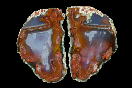 A cross section of the agate stone. At the top the pseudomorphosis divide agate, slanting thermal cracks are at the bottom. Multicolored silica rings colored with metal oxides are visible. Origin: Asni, Atlas Mountains, Morocco. Stock Photo