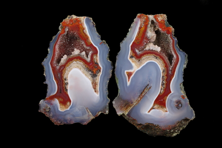 A cross section of the agate stone. At the top quartz geode with calcite, bottom pseudomorph. Multicolored silica bands colored with metal oxides are visible. Origin: Asni, Atlas Mountains, Morocco.