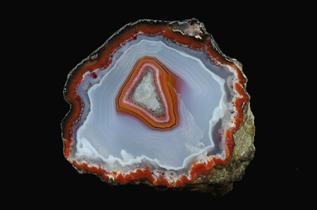 A cross section of the agate stone. Colorful center against the background of gray-blue and white chalcedony. Origin: Asni, Atlas Mountains, Morocco. Stock Photo