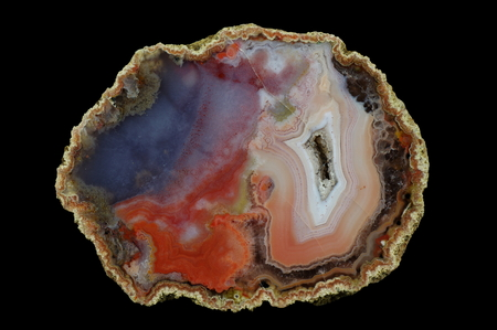 A cross section of the agate stone with quartz geode. Concentric with right and clouded left. Multicolored silica rings colored with metal oxides are visible. Origin: Asni, Atlas Mountains, Morocco.