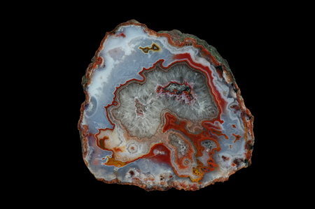 A cross section of the agate stone. The center is filled with quartz. Multicolored silica rings colored with metal oxides are visible. Origin: Asni, Atlas Mountains, Morocco.