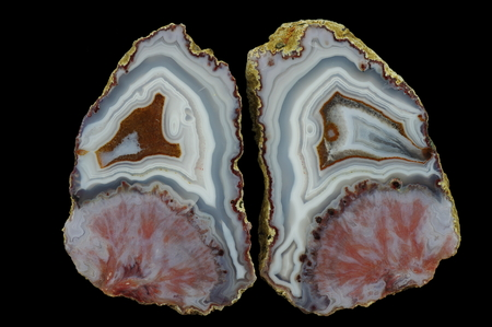 A cross section of the agate stone. At the top is concentric agate, at the bottom pseudomorphosis after the spheroidal concentration of minerals. Multicolored silica rings colored with metal oxides are visible. Origin: Asni, Atlas Mountains, Morocco. Stock Photo