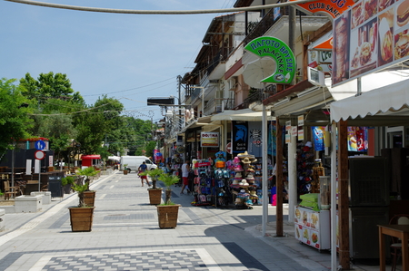 Stavros, small town near Chalkidiki peninsula in northen Greece, region of Macedonia. Main street in the city with shops and pubs. On the street there are some tourists.