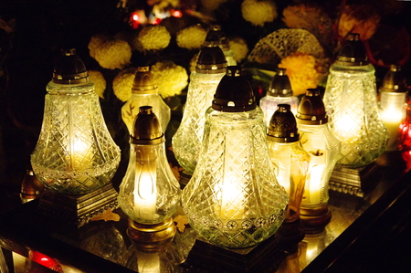 Evening at the cemetery. On the grave are burning candles, close-up.
