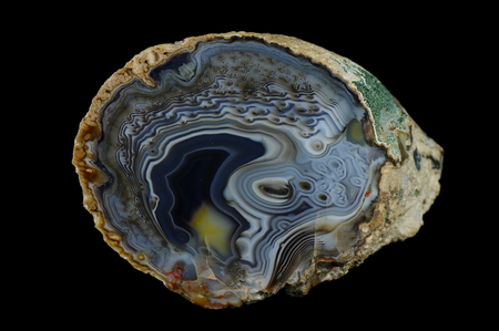 A cross section of agate stone. Agate irregularly meshed. Multicolored silica rings colored with metal oxides are visible. Origin: Rudno near Krakow, Poland.