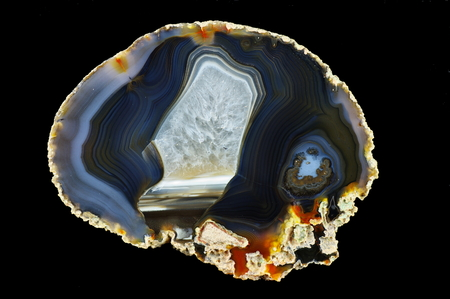 A cross section of agate stone. Multicolored silica bands colored with metal oxides are visible. Horizontal agate filled with quartz. Origin: Rudno near Krakow, Poland. Stock Photo