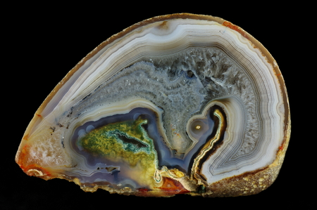 A cross section of agate stone. Multicolored silica bands colored with metal oxides are visible. Agate with quartz-agate fill, irregularly meshed. Origin: Rudno near Krakow, Poland.