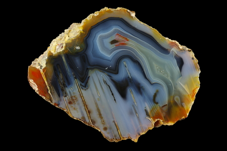 A cross section of agate stone. Multicolored silica bands colored with metal oxides are visible. Stalactite agate. Origin: Rudno near Krakow, Poland.
