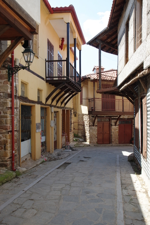 Arnea, Greece, June 13, 2017: small town near the Chalkidiki peninsula in northen greece. Region of Macedonia. Street in the city center. Along the road are houses with typical architecture of the region.