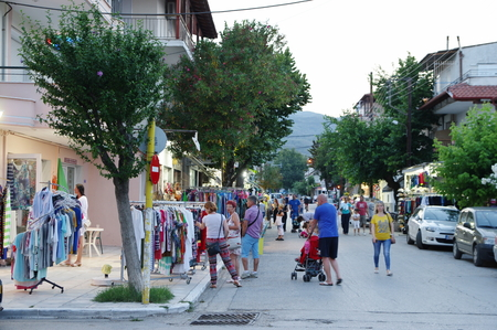 Asprovalta, Greece, June 16, 2017: summer resort in northern Greece on the Aegean Sea. Street in the evening. Visible numerous shops, taverns and strolling tourists.
