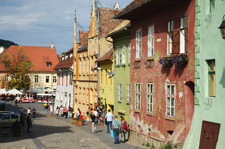Sighisoara, Transylvania, Romania – September 12, 2017: medieval old town surrounded by defensive walls. Buildings typical for the region.