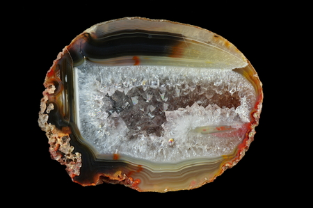 A cross-section of agate. Multicolored silica bands colored with metal oxides are visible. Horizontal agate, filled with quartz, with geode. Origin: Rudno near Krakow, Poland.