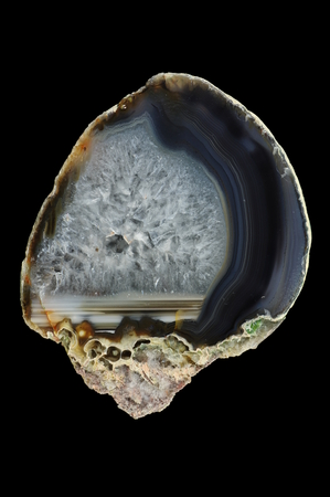 A cross-section of agate. Horizontal agate, filled with quartz. Multicolored silica rings colored with metal oxides are visible. Origin: Rudno near Krakow, Poland. Stock Photo