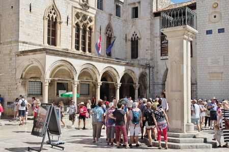 Dubrovnik, Dalmacija, Croatia – September 11, 2018: Luza Square, Old Town. City Hall and Marin Drzic's National Theatre. Many tourists are walking along the street.