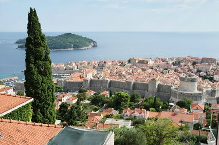 Dubrovnik, Dalmacija, Croatia – September 11, 2018: a general view from above of the old city. You can see defensive walls with towers and old Town. On the left tere is a port. On the sea tere  에디토리얼
