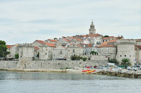 The city of Korcula on the island of Korcula, Croatia – September 13, 2018: A view of the city from the sea. You can see the defensive walls with towers and the old Town.